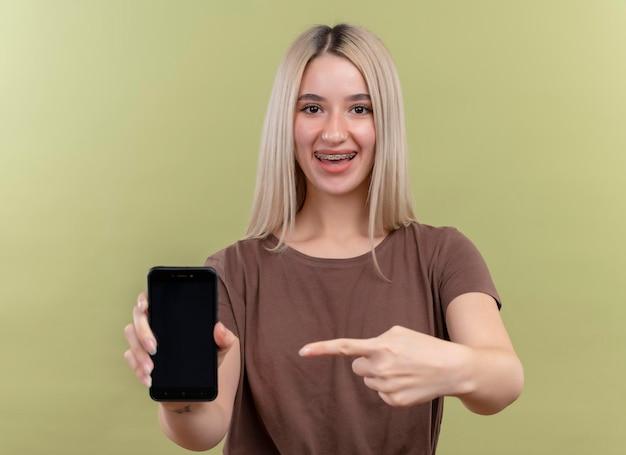 Freudiges junges blondes mädchen in zahnspangen, die handy halten, das auf lokalisierte grünfläche zeigt