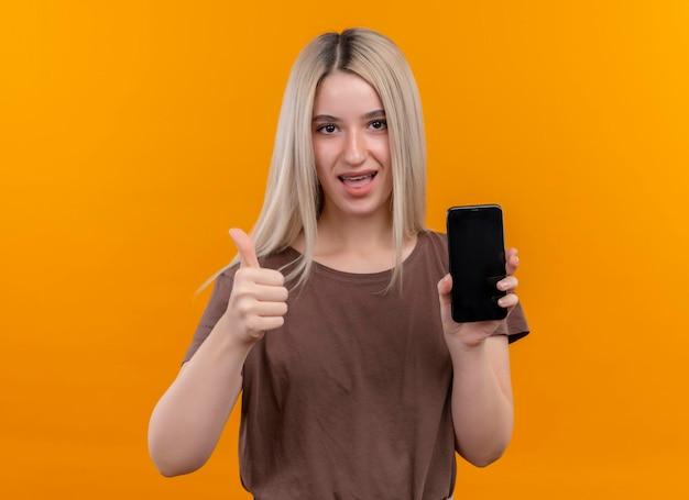 Freudiges junges blondes mädchen in zahnspangen, die handy halten daumen oben auf lokalisiertem orange raum mit kopienraum zeigen