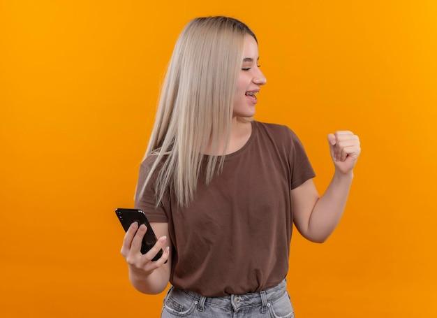 Freudiges junges blondes mädchen in zahnspangen, die handy mit erhabener faust auf lokalisiertem orange raum mit kopienraum halten