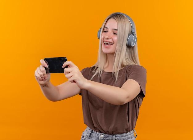 Freudiges junges blondes mädchen in zahnspangen, die kopfhörer tragen, die handy halten, das es auf lokalisiertem orange raum mit kopienraum betrachtet
