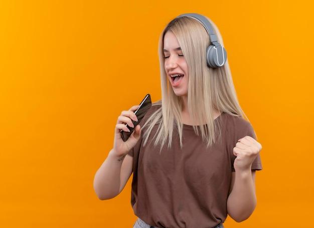Freudiges junges blondes mädchen in zahnspangen, die kopfhörer tragen, die unter verwendung des telefons als mikrofon mit erhabener hand und geschlossenen augen auf isoliertem orange raum mit kopienraum singen