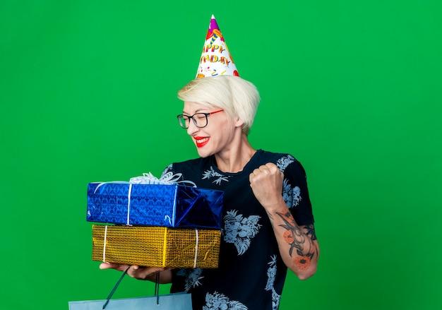 Freudiges junges blondes partygirl, das brille und geburtstagskappe hält, die papiertüte und geschenkboxen hält, die ja geste lokalisiert auf grünem hintergrund mit kopienraum tun
