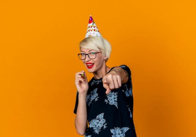 Freudiges junges blondes partygirl, das brille und geburtstagskappe hält, die partygebläse halten und auf kamera lokalisiert auf orange hintergrund mit kopienraum zeigt