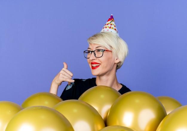 Freudiges junges blondes partygirl, das brille und geburtstagskappe trägt, die hinter luftballons steht, die seite betrachten, hängen lose geste lokalisiert auf lila hintergrund