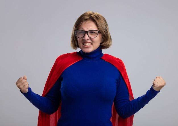 Freudiges junges blondes superheldenmädchen im roten umhang, der die brille trägt, die seite tut, die ja geste lokalisiert auf weißem hintergrund tut