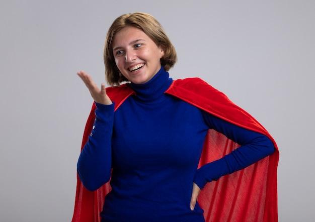 Freudiges junges blondes superheldenmädchen im roten umhang, der hand auf taille und ein anderes in der luft hält, die unten auf weißem hintergrund schaut