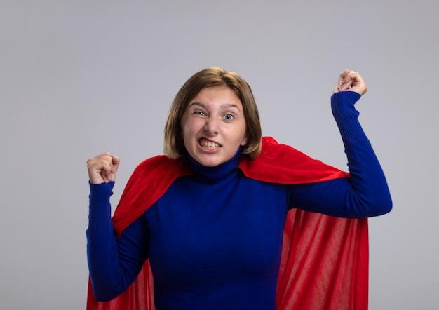 Freudiges junges blondes superheldenmädchen im roten umhang, der kamera betrachtet, die ja geste lokalisiert auf weißem hintergrund tut