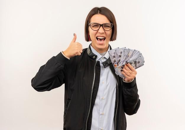 Freudiges junges callcenter-mädchen, das eine brille trägt, die geld hält und daumen auf weiß lokalisiert zeigt