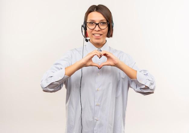 Freudiges junges callcenter-mädchen, das eine brille und ein headset trägt, die das herzzeichen tun, das die zunge lokalisiert auf weiß zeigt