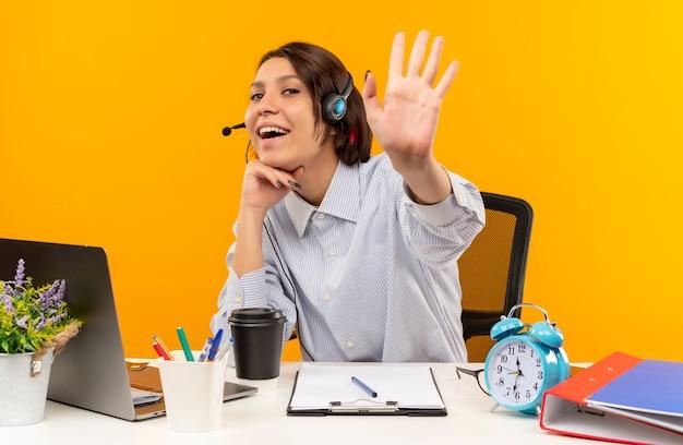 Freudiges junges callcenter-mädchen, das headset trägt, das am schreibtisch sitzt, hand unter kinn setzt und hallo gestikuliert auf orange lokalisiert