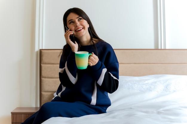 Freudiges junges hübsches kaukasisches mädchen, das auf bett im schlafzimmer sitzt und tasse hält, die seite schaut und am telefon spricht