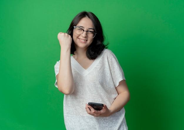Freudiges junges hübsches kaukasisches mädchen, das die brille trägt, die das handy zwinkert und hält und die faust lokalisiert auf grünem hintergrund mit kopienraum anhebt