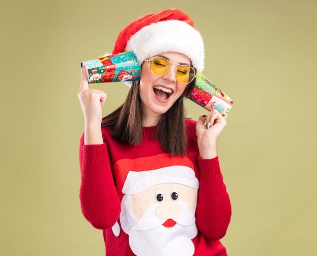 Freudiges junges hübsches kaukasisches mädchen, das weihnachtsmann-pullover und hut mit gläsern hält, die plastikweihnachtsbecher neben ohren halten, die gespräche mit geschlossenen augen hören