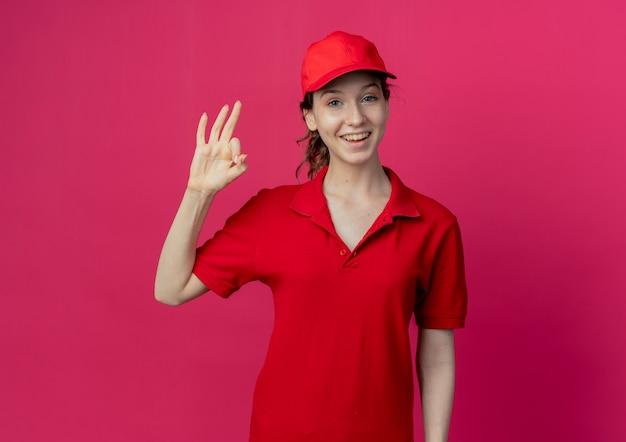 Freudiges junges hübsches liefermädchen in der roten uniform und in der kappe, die ok zeichen lokalisiert auf purpurrotem hintergrund mit kopienraum tun