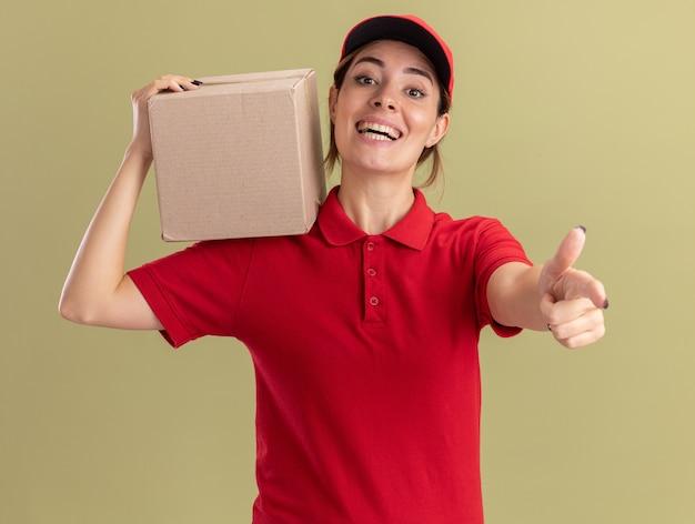 Freudiges junges hübsches liefermädchen in uniform hält karton und zeigt auf kamera auf olivgrün