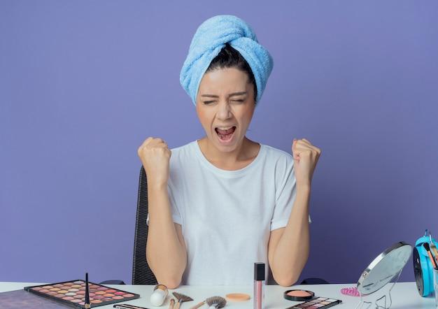 Freudiges junges hübsches mädchen, das am make-up-tisch mit make-up-werkzeugen und mit badetuch auf kopf geballten fäusten mit geschlossenen augen lokalisiert auf lila hintergrund sitzt