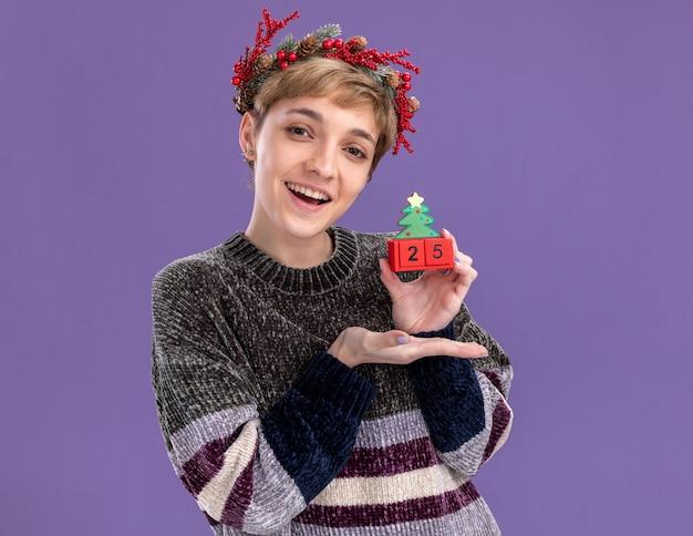 Freudiges junges hübsches mädchen, das weihnachtskopfkranz trägt, der weihnachtsbaumspielzeug mit datum zeigt, das auf kamera betrachtet, die auf lila hintergrund lokalisiert wird