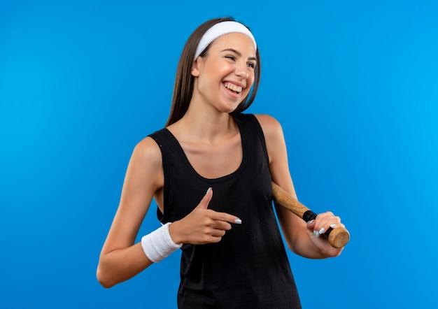 Freudiges junges hübsches sportliches mädchen, das stirnband und armband hält, das baseballschläger hält und auf seite lokalisiert auf blauem raum schaut
