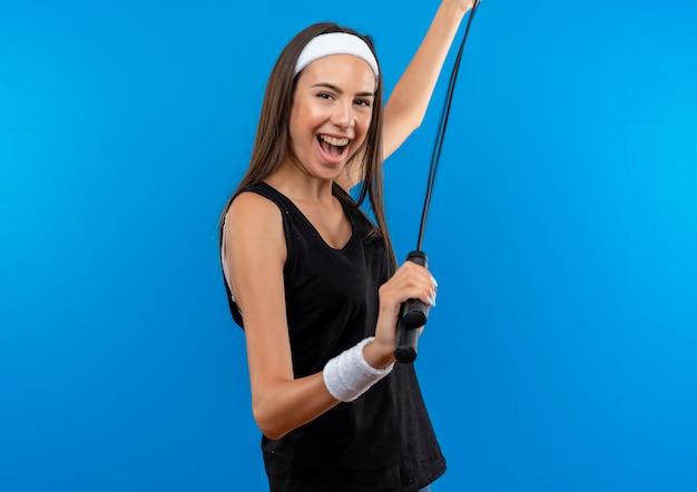 Freudiges junges hübsches sportliches mädchen, das stirnband und armband hält springseil lokalisiert auf blauem raum trägt