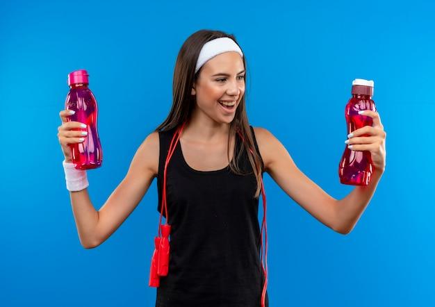 Freudiges junges hübsches sportliches mädchen, das stirnband und armband trägt und wasserflaschen mit springendem seil um ihren hals lokalisiert auf blauem raum hält und betrachtet
