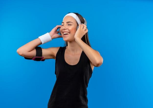 Freudiges junges hübsches sportliches mädchen, das stirnband und armband und kopfhörer mit telefonarmband trägt und musik mit geschlossenen augen hört