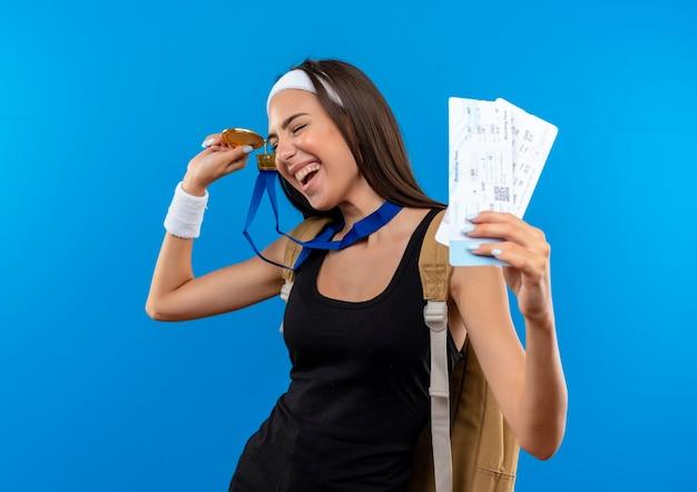 Freudiges junges hübsches sportliches mädchen, das stirnband und armband und rückentasche mit medaille um hals hält, die flugtickets und medaille mit geschlossenen augen lokalisiert auf blauem raum hält