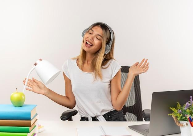 Freudiges junges hübsches studentenmädchen, das kopfhörer trägt, sitzt am schreibtisch mit schulwerkzeugen, die musik hören, die leere hände mit geschlossenen augen lokalisiert auf weiß zeigt