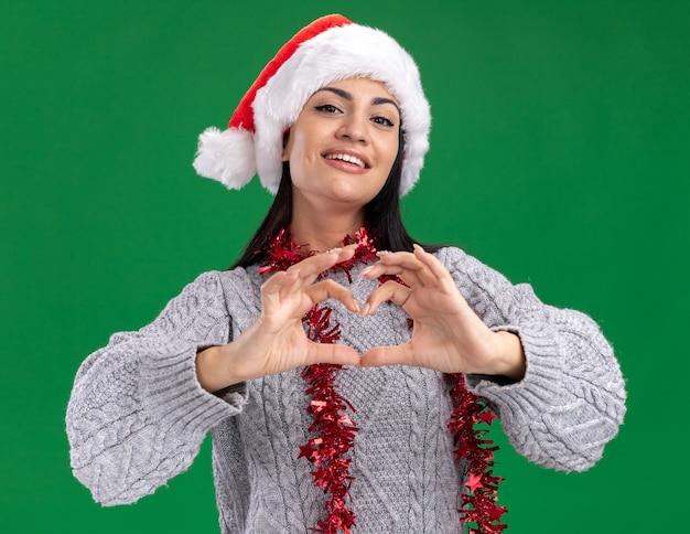 Freudiges junges kaukasisches mädchen, das weihnachtshut und lametta-girlande um den hals trägt und kamera betrachtet, die herzzeichen lokalisiert auf grünem hintergrund tut