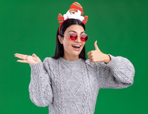 Freudiges junges kaukasisches mädchen, das weihnachtsmann-stirnband mit brille trägt, die kamera zeigt, die leere hand und daumen oben auf grünem hintergrund zeigt