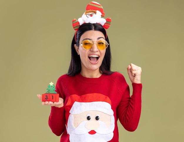 Freudiges junges kaukasisches mädchen, das weihnachtsmann-stirnband und pullover mit brille trägt, die weihnachtsbaumspielzeug mit dem datum zwinkert, das ja geste lokalisiert auf olivgrüner wand tut