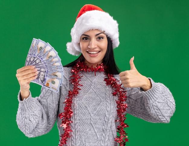 Freudiges junges kaukasisches mädchen, das weihnachtsmütze und lametta-girlande um den hals hält, der geld betrachtet, das kamera betrachtet daumen oben auf grünem hintergrund zeigt