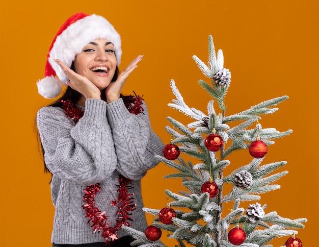 Freudiges junges kaukasisches mädchen, das weihnachtsmütze und lametta-girlande um den hals trägt, der nahe verziertem weihnachtsbaum steht und kamera betrachtet, die hände unter kinn lokalisiert auf orange hintergrund hält