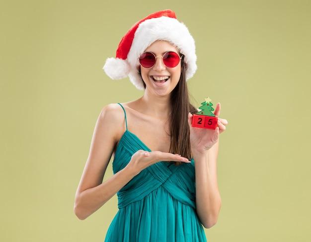 Freudiges junges kaukasisches mädchen in der sonnenbrille mit der weihnachtsmannmütze, die weihnachtsbaumverzierung mit hand hält und zeigt