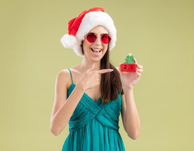 Freudiges junges kaukasisches mädchen in der sonnenbrille mit der weihnachtsmütze, die auf weihnachtsbaumverzierung hält und zeigt