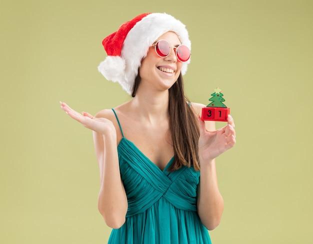 Freudiges junges kaukasisches mädchen in sonnenbrille mit weihnachtsmütze, die weihnachtsbaumverzierung hält und seite betrachtet