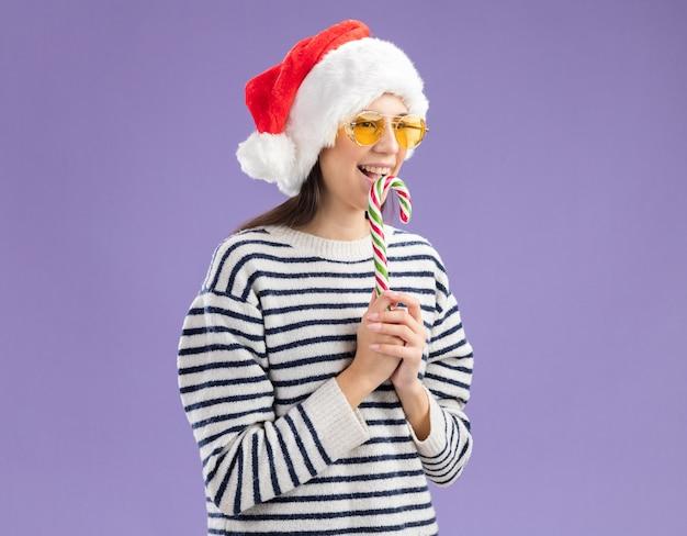 Freudiges junges kaukasisches mädchen in sonnenbrille mit weihnachtsmütze, die zuckerstange hält und seite betrachtet