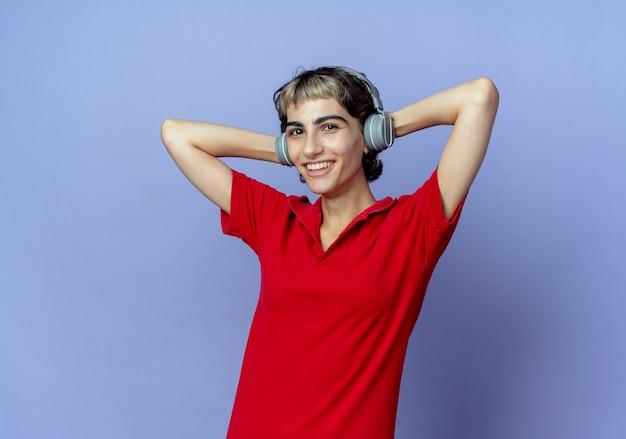 Freudiges junges kaukasisches mädchen mit pixie-haarschnitt, das kopfhörer trägt, die hände hinter kopf lokalisiert auf lila hintergrund mit kopienraum setzen
