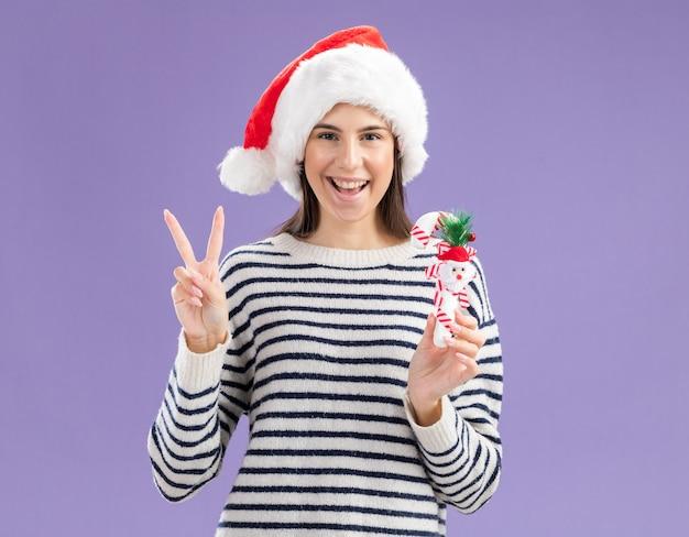 Freudiges junges kaukasisches mädchen mit weihnachtsmütze, die zuckerstange hält und siegeszeichen gestikuliert