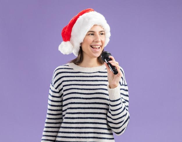 Freudiges junges kaukasisches mädchen mit weihnachtsmütze hält mikrofon, das seite schaut