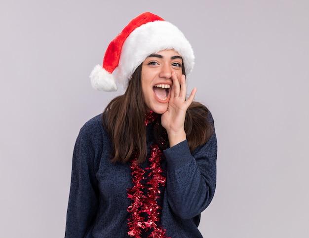 Freudiges junges kaukasisches mädchen mit weihnachtsmütze und girlande um den hals hält hand nahe an mund, der jemanden ruft
