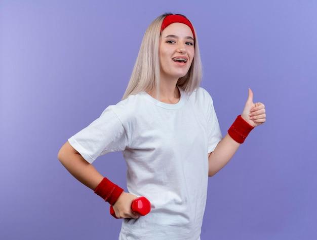Freudiges junges kaukasisches sportliches mädchen mit zahnspangen, die stirnband tragen