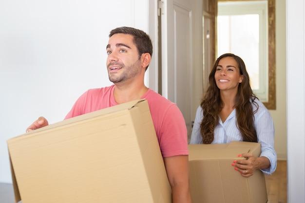 Freudiges junges lateinisches paar, das in ihrer neuen wohnung mit kartons kommt
