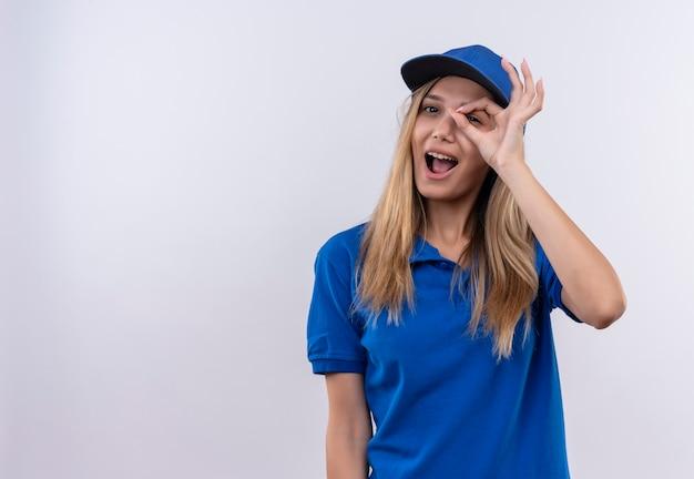 Freudiges junges liefermädchen, das blaue uniform und kappe trägt, die blickgestik lokalisiert auf weißer wand mit kopienraum zeigt
