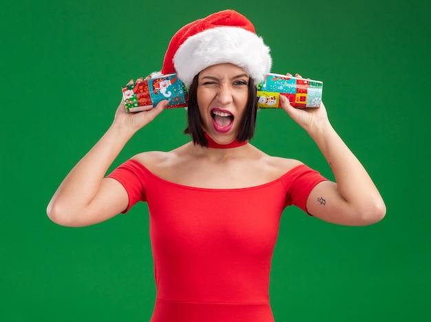 Freudiges junges mädchen, das weihnachtsmütze hält, die plastikweihnachtsbecher neben ohren hält, die gespräch hören, das lokalisiert auf grüner wand zwinkert