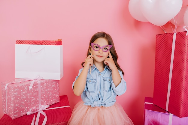 Freudiges junges mädchen des porträts im blauen hemd, das maske auf gesicht umgibt bunte geschenkboxen auf rosa hintergrund. schöne süße momente der kleinen prinzessin, ziemlich freundliches kind
