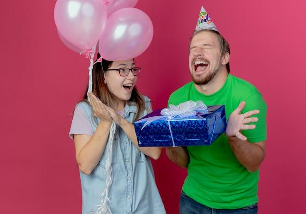 Freudiges junges mädchen hält heliumballons, die aufgeregten jungen mann betrachten, der partyhut trägt, hält geschenkbox lokalisiert auf rosa wand