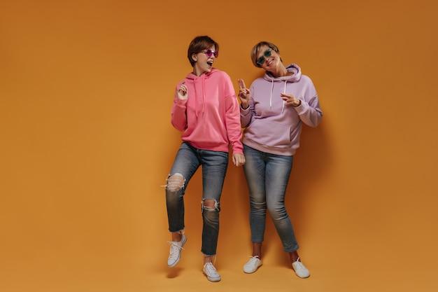 Freudiges junges mädchen im rosa sweatshirt, das mit der kühlen dame im lila kapuzenpulli eine grüne sonnenbrille auf orange lokalisiertem hintergrund tanzt.