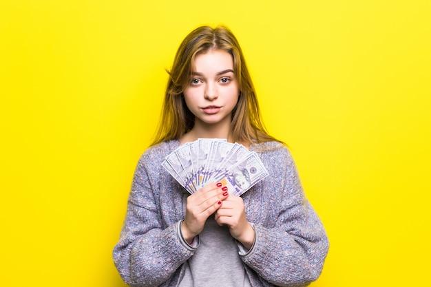 Freudiges junges mädchen mit dollars in ihren händen isoliert
