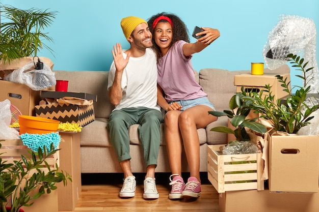 Freudiges junges paar, das auf der couch sitzt, umgeben von kisten