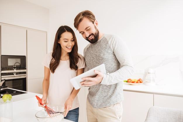 Freudiges junges paar, das gebäck kocht